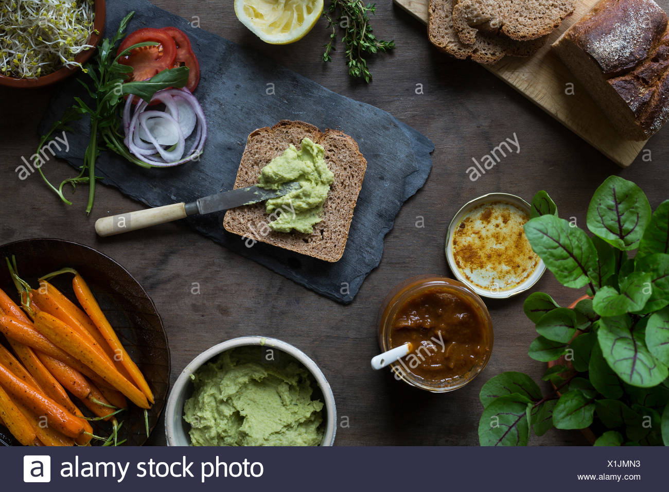 La préparation des sandwichs vegan pour pique-nique avec des carottes, des rôties, de pois et de feuilles vertes. Vue d'en haut Photo Stock