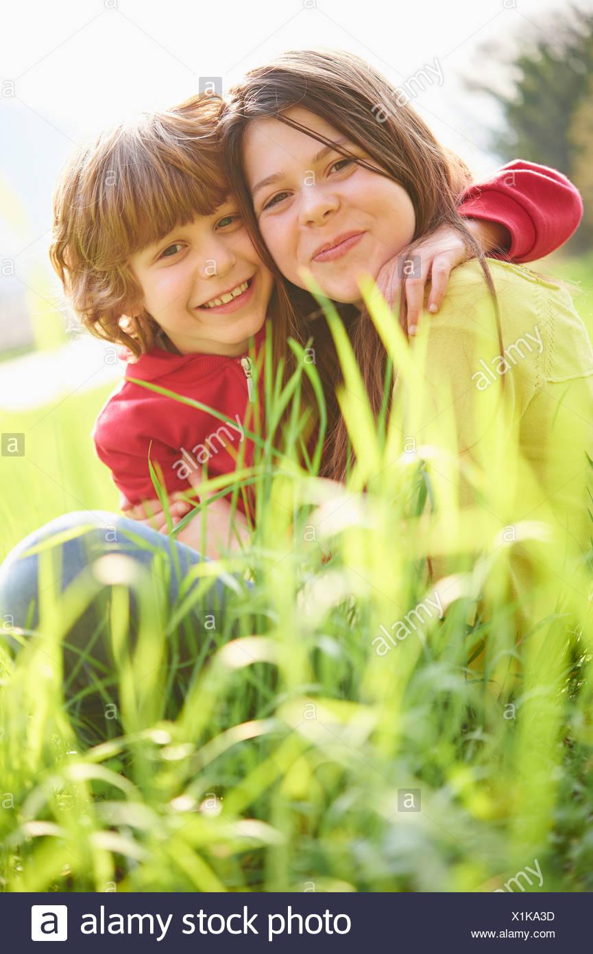 Soeur et frère cadet sitting in grassy field Photo Stock