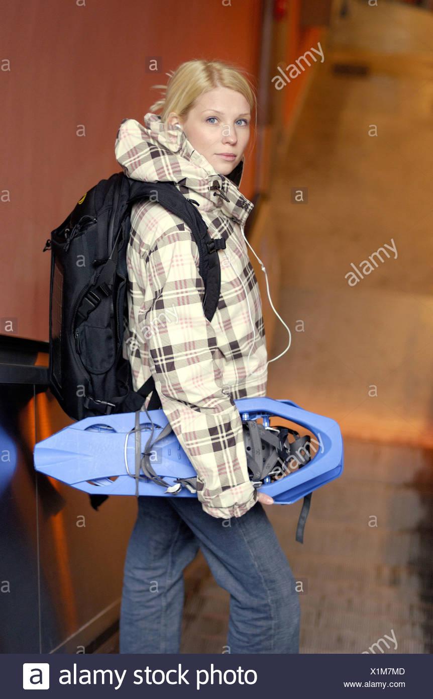 Jeune femme avec sac à dos, et d'un lecteur MP3 sur l'escalator permanent Photo Stock