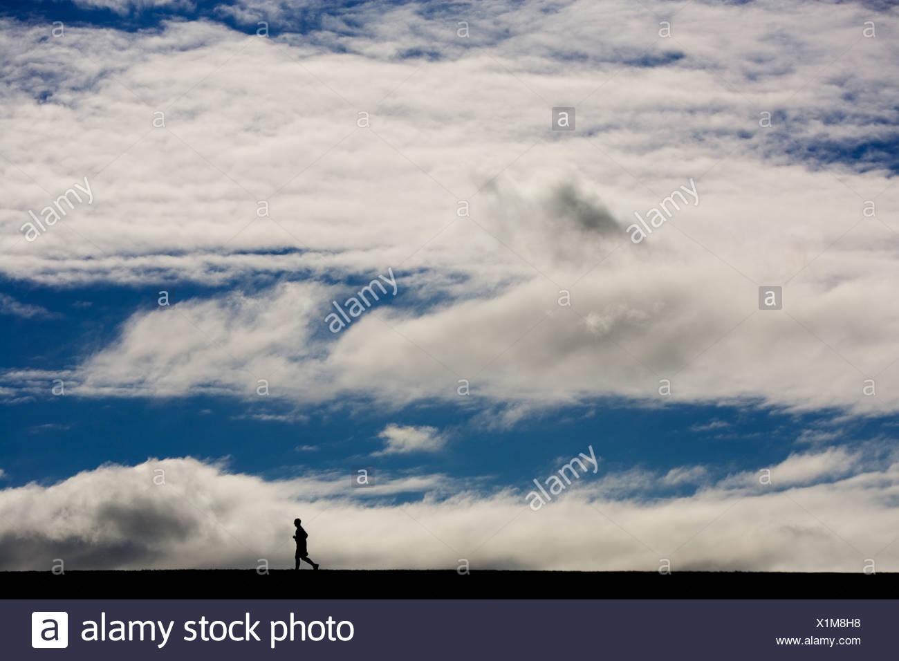 Un homme qui court un marathon avec ciel bleu et nuages blancs au-dessus de lui à Lincoln, Nebraska (Silhouette). Photo Stock