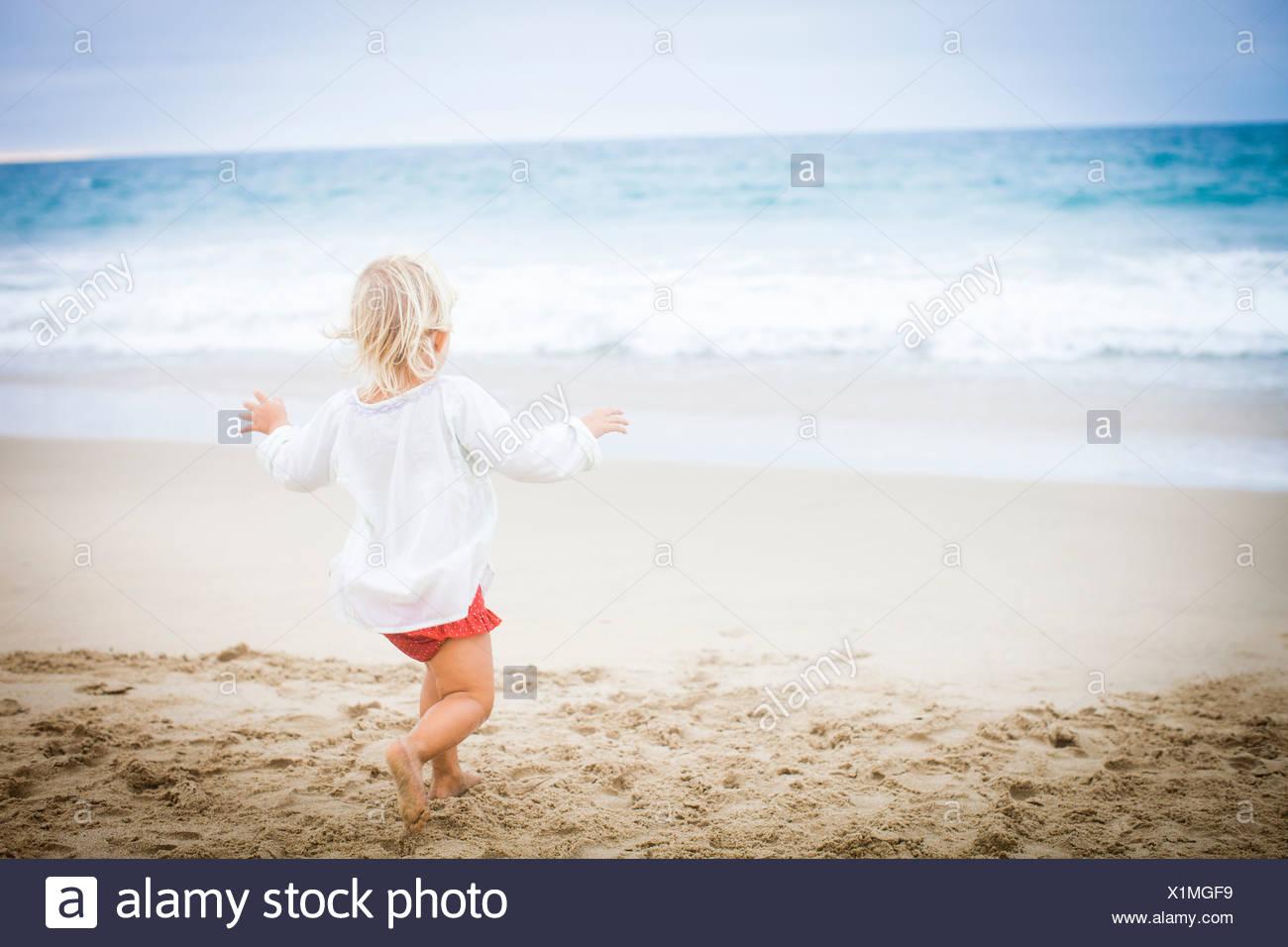 Vue arrière de fille courir vers la mer Photo Stock