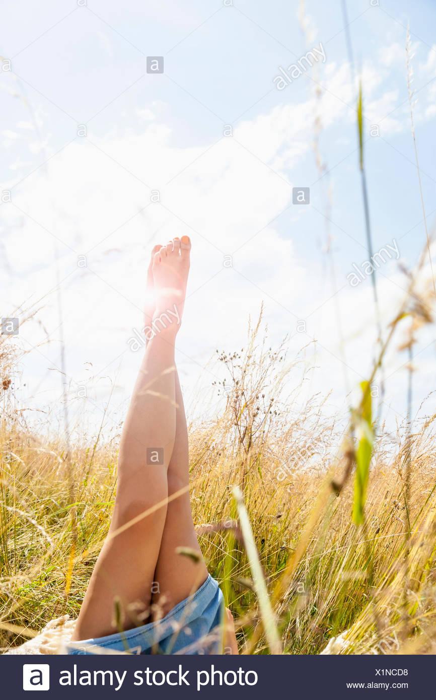 Jeune femme jambes nues dans la zone d'herbes hautes Photo Stock