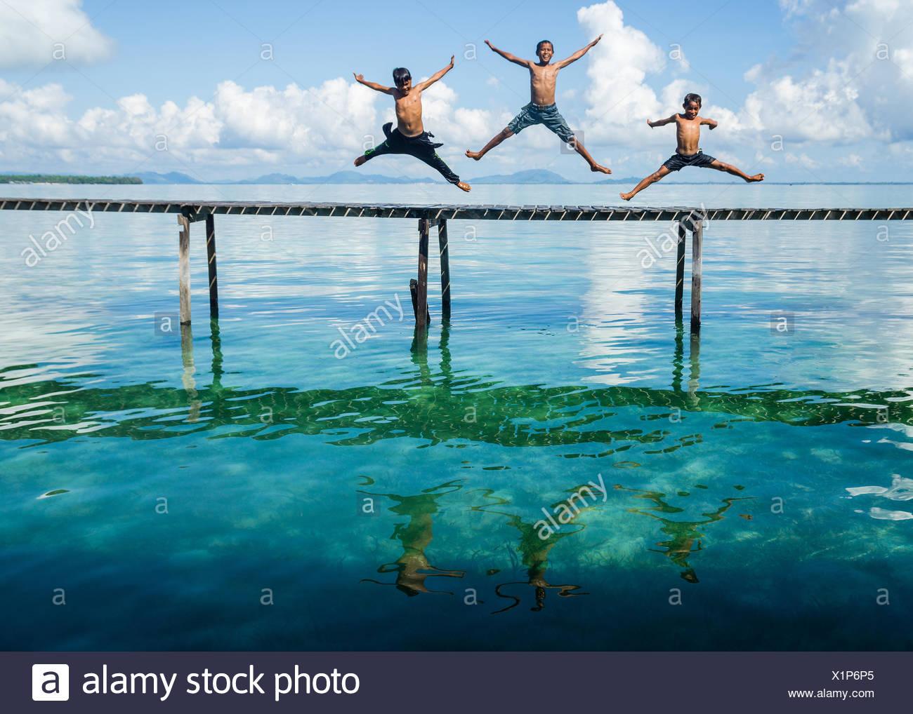 Trois garçons en sautant à la mer à partir d'une jetée, Salakan Island, Semporna, Sabah, Malaisie Photo Stock