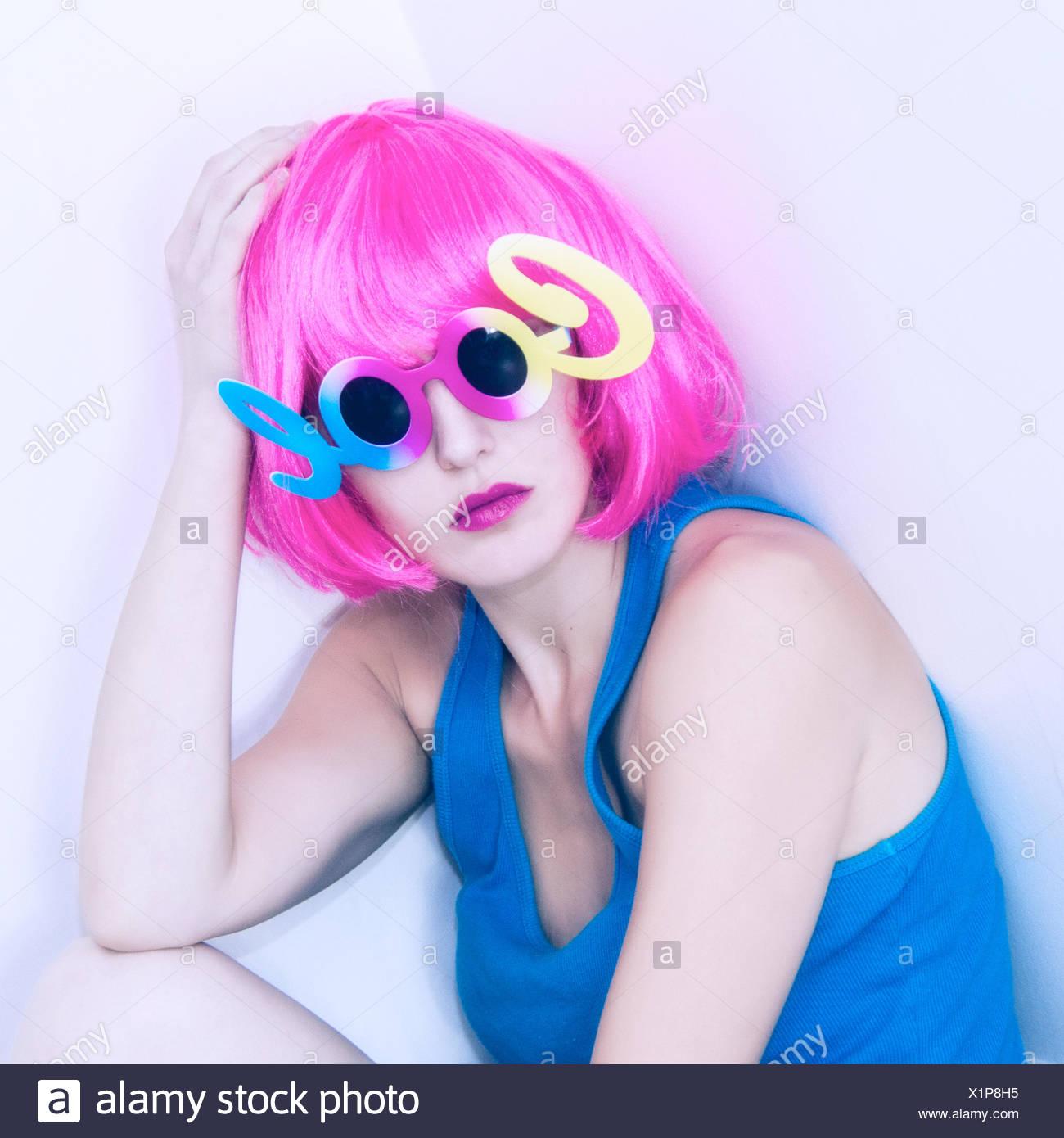 Portrait de femme en perruque rose et lunettes cool Photo Stock