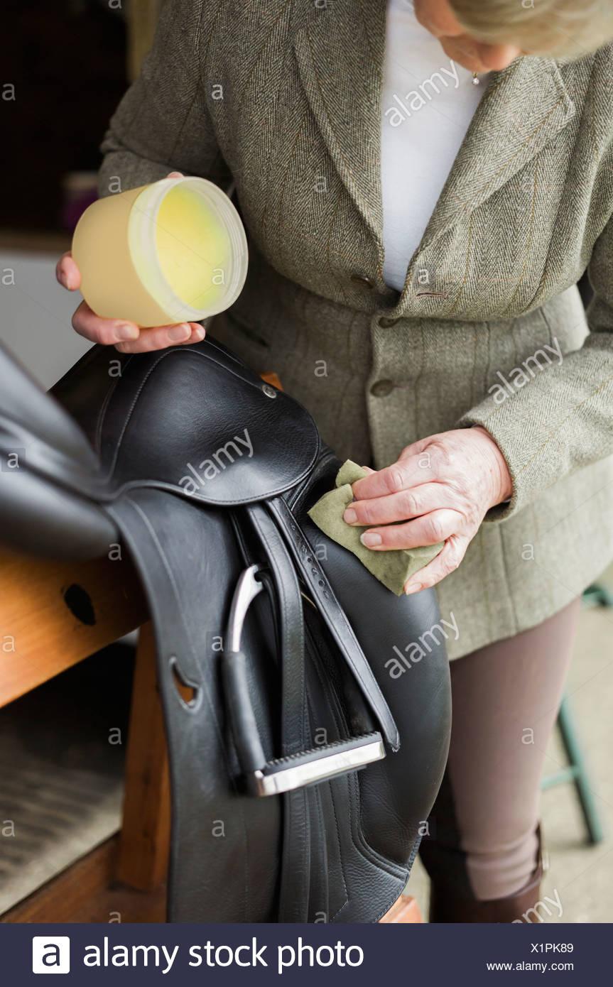 Une femme le nettoyage et la préparation tactique et selle dans la cour d'une école d'. Banque D'Images