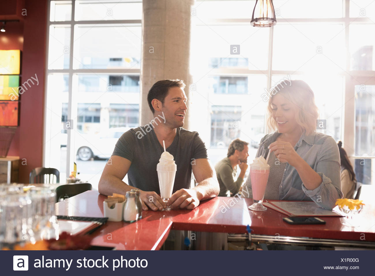 Jeune couple drinking milkshakes à diner counter Photo Stock