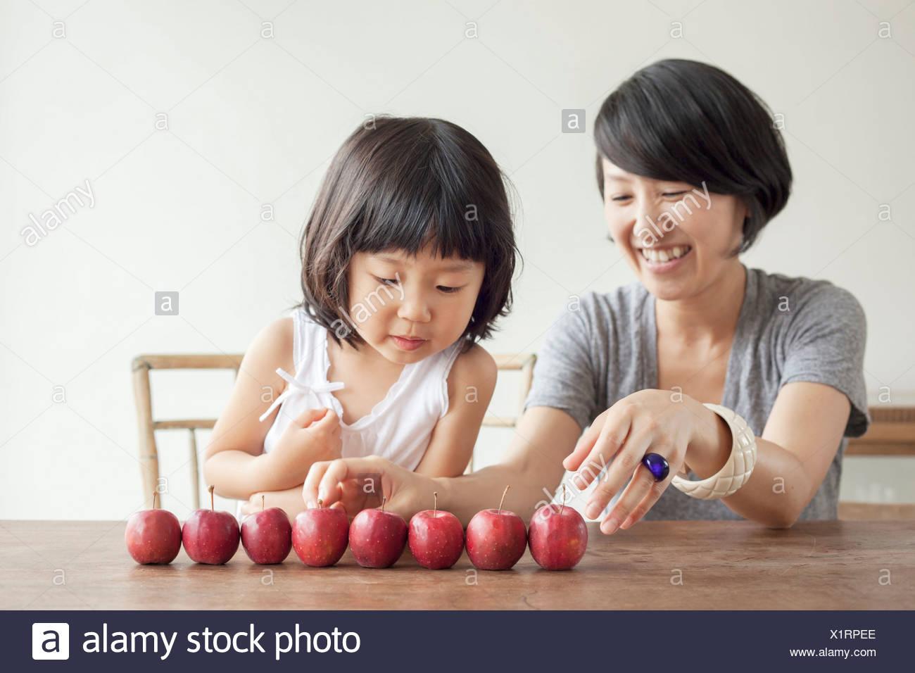 Mère et fille avec des pommes rouges dans une rangée Photo Stock