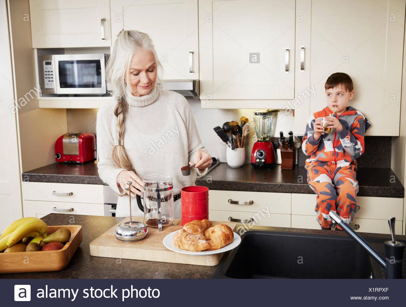 Grand-mère faire le café, petit-fils assis sur le comptoir de la cuisine Photo Stock