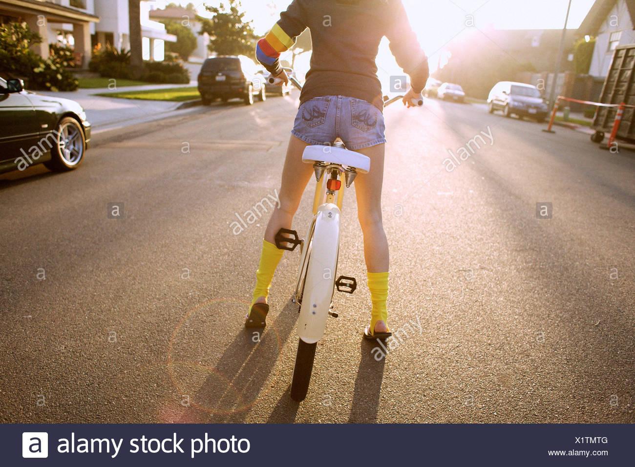 Jeune femme portant des chaussettes jaunes et un hoodie se prépare à lancer un cheval, en vtt. Photo Stock