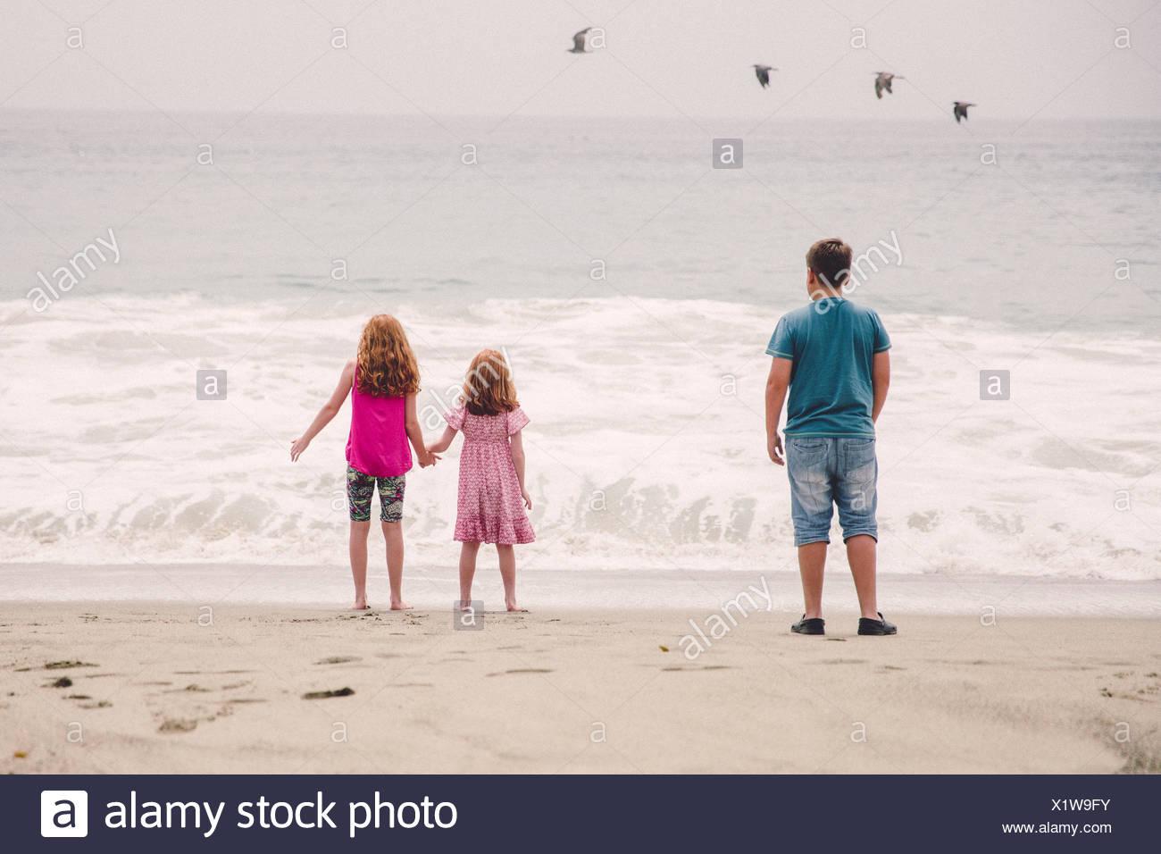 USA, Californie, Los Angeles, les enfants (6-7, 8-9, 12-13) regardant des vagues se brisant sur la plage Photo Stock