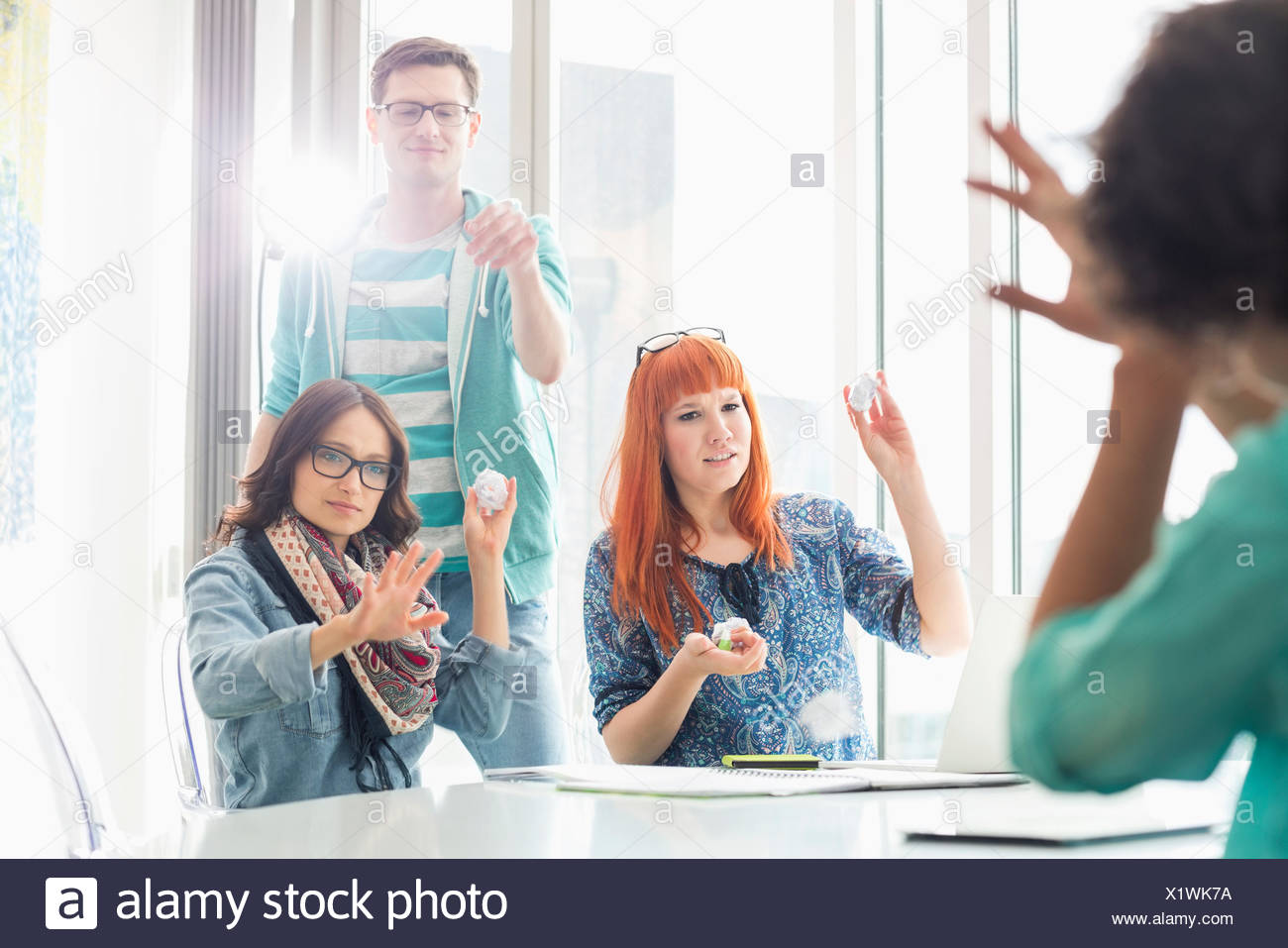 Angry woman throwing paper balls sur collègue in creative office Photo Stock