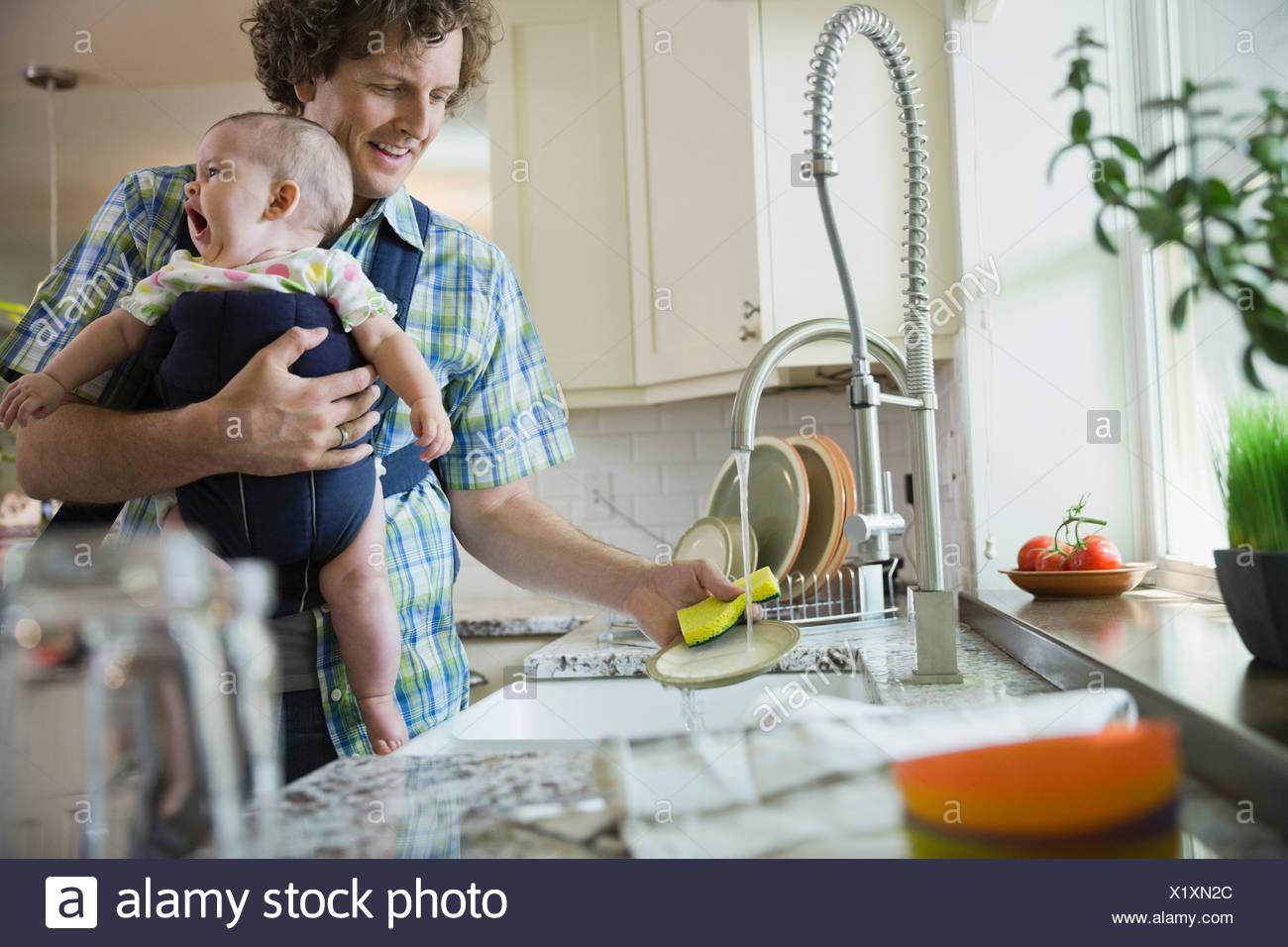 Père de vaisselle tout en portant bébé fille Photo Stock