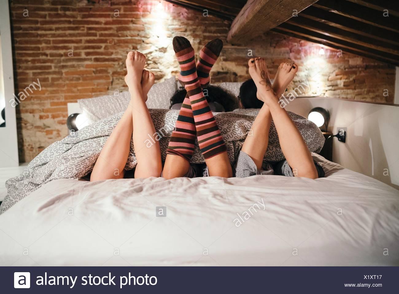 Jambes croisées d'amis situées côte à côte sur le lit Photo Stock