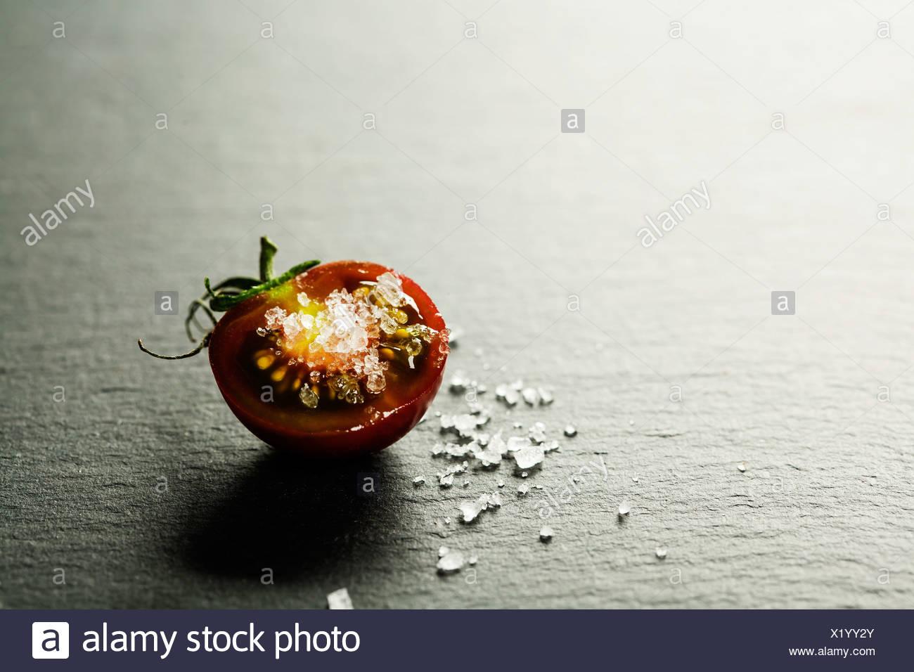 Tomates Raisins frais avec du sel pour une utilisation comme ingrédients de cuisson de moitié avec une tomate dans le premier plan avec copyspace Photo Stock