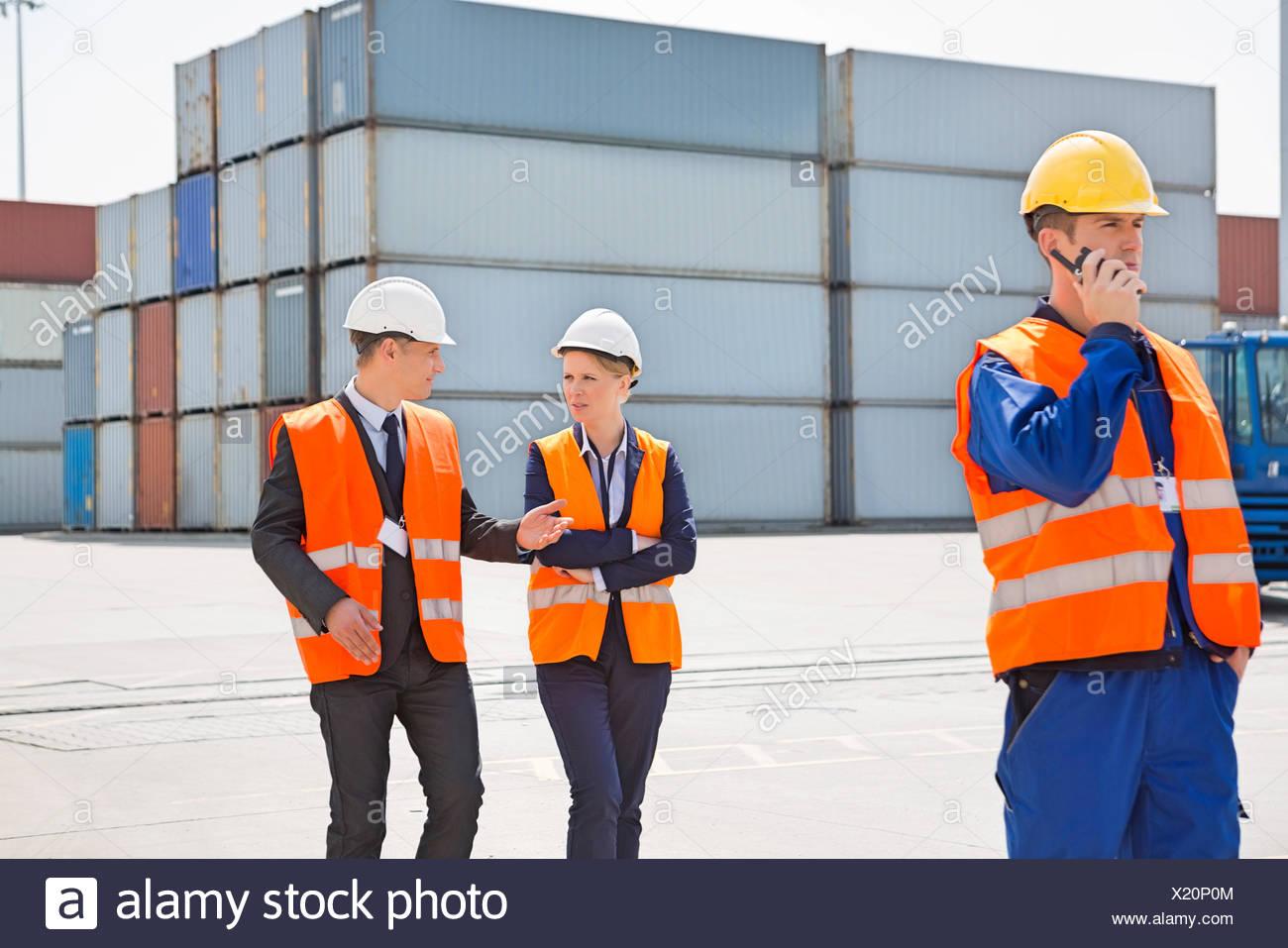 À l'aide de travailleurs talkie-walkie tandis que ses collègues discutant en cour d'expédition Photo Stock