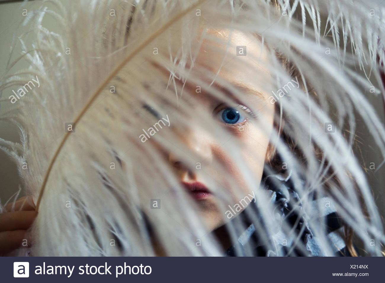 Fille avec une plume devant son visage Photo Stock