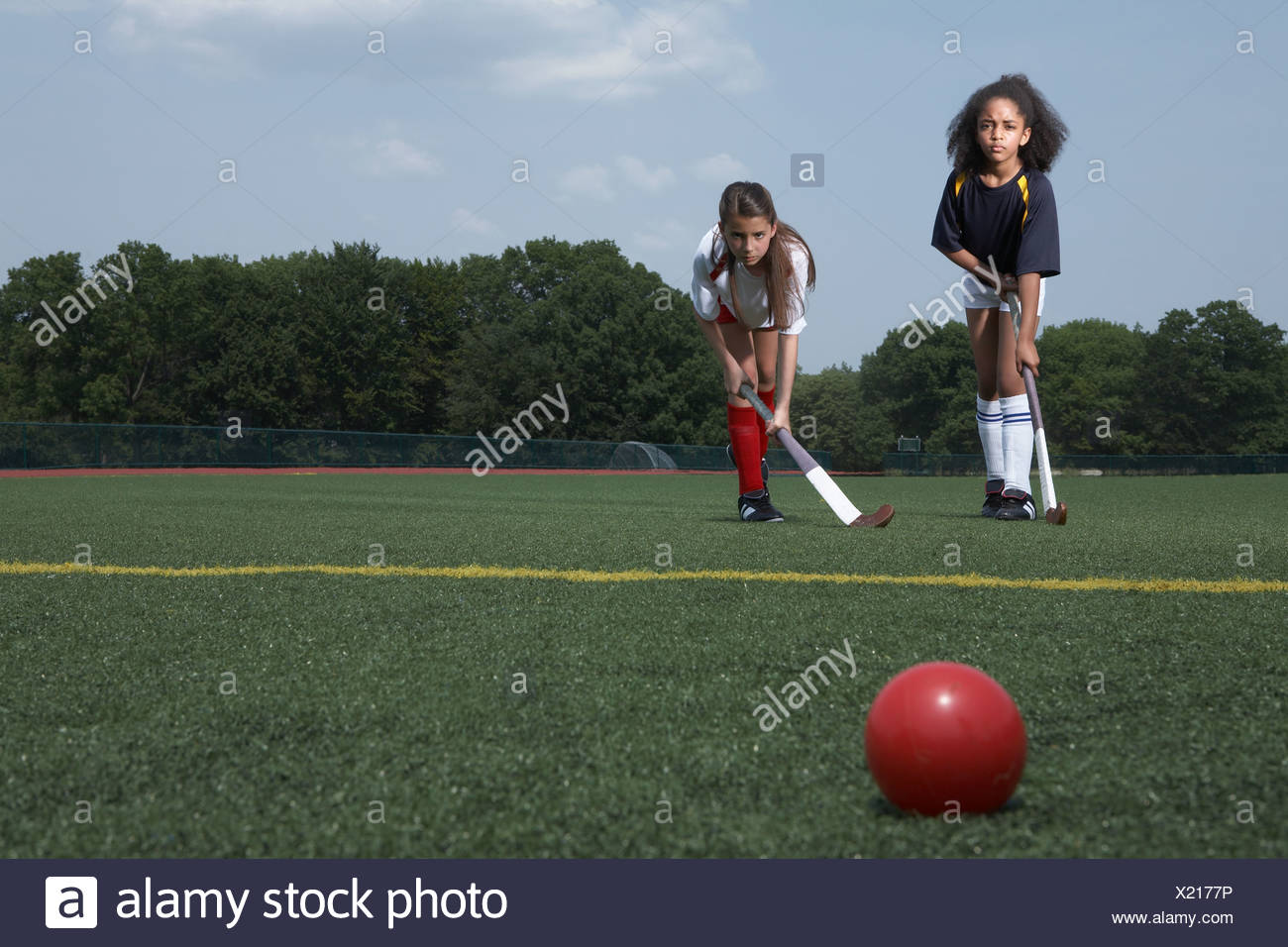 Deux jeunes filles jouant au hockey Photo Stock
