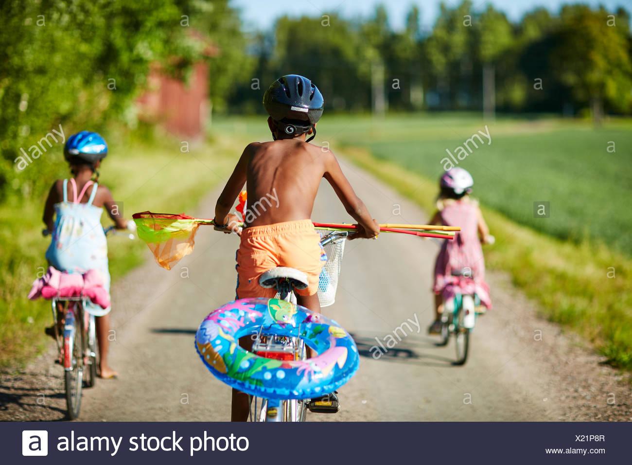 Les enfants à vélo sur une route rurale à Gullspang, Suède Photo Stock
