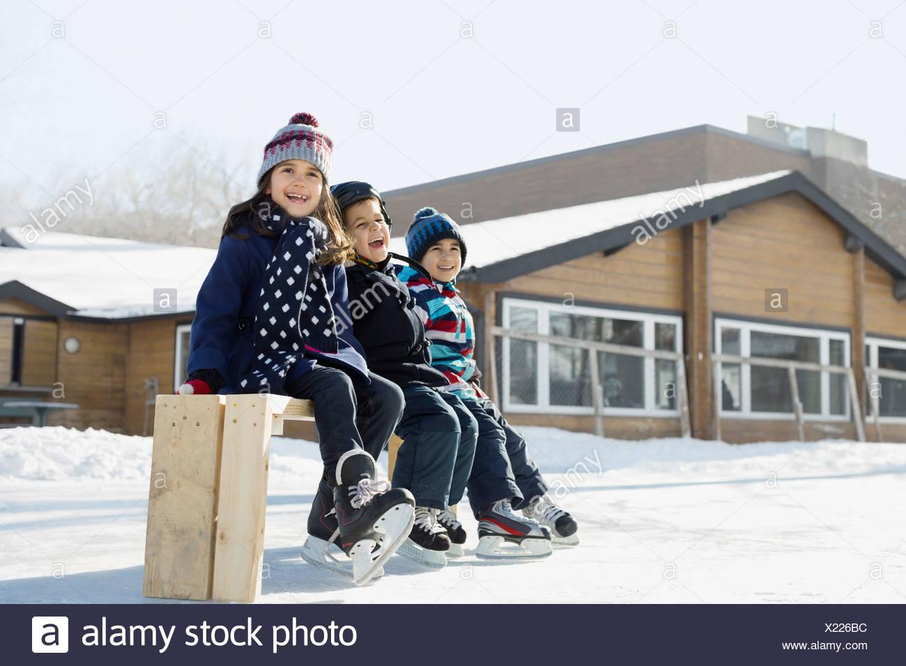 Frères et soeurs assis sur le banc de la patinoire Photo Stock