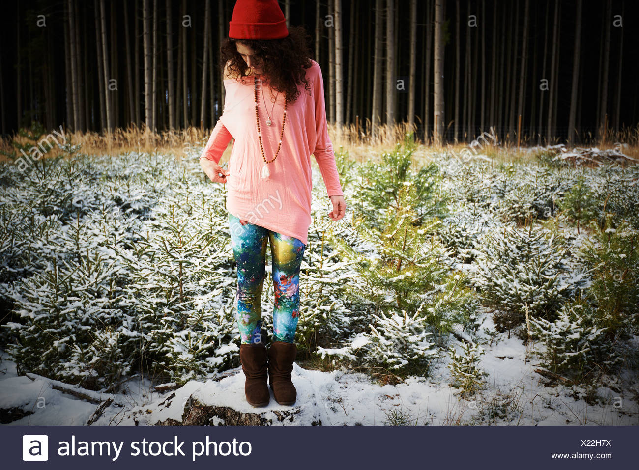Mid adult woman in hat, debout sur sol couvert de neige Photo Stock