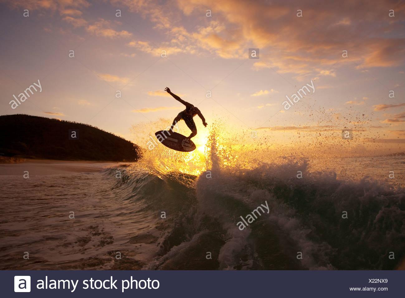 Hawaii, Maui, Makena, Skimboarder obtient Big Air déclenché une vague au coucher du soleil Photo Stock