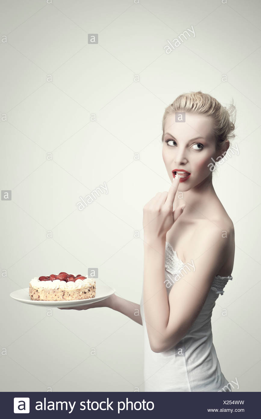 Young woman holding strawberry cake, le léchage crème par doigt, portrait Photo Stock
