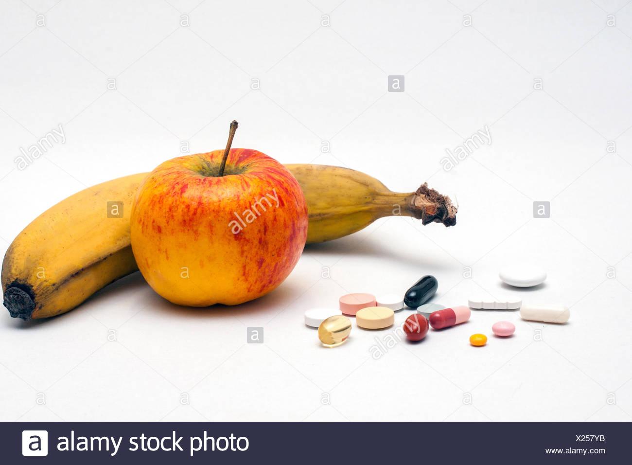 Verschiedene bunte Tabletten, Apfel und Banane, isoliert Banque D'Images