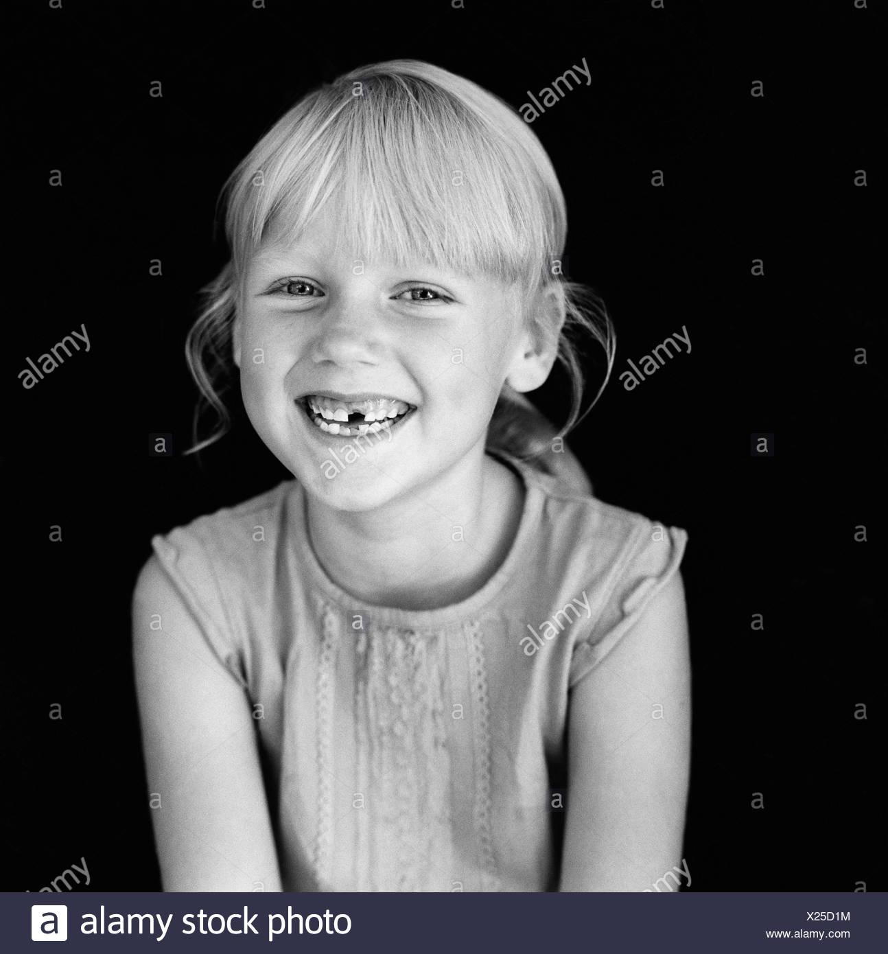 Blonde en noir et blanc seules les filles enfants heureux à l'intérieur d'une seule personne portrait optimisme souriant positives sans dents dent Photo Stock