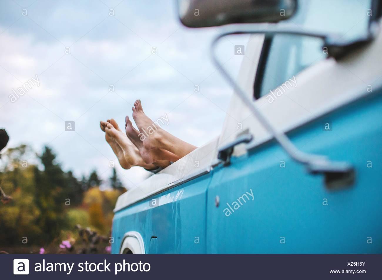 Jeune couple couché à l'arrière du camion, les pieds nus sur le bord du chariot, l'accent sur pieds Photo Stock