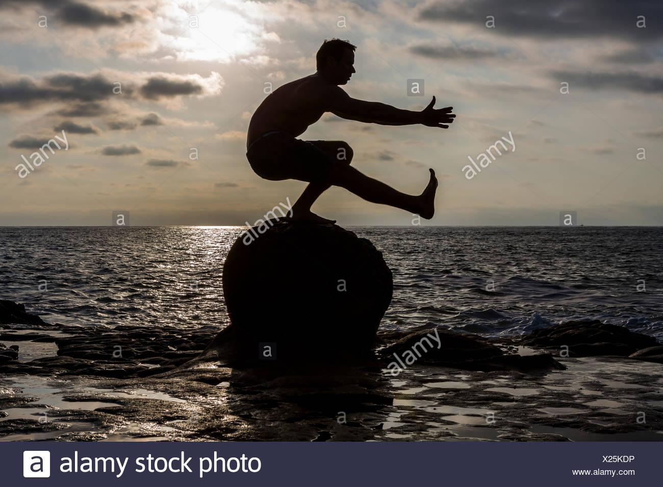 La silhouette d'un homme torse nu comme athlète CrossFit il effectue un pistolet ou squat à une jambe sur un rocher dans l'océan Pacifique à San Diego, Californie au coucher du soleil. Photo Stock