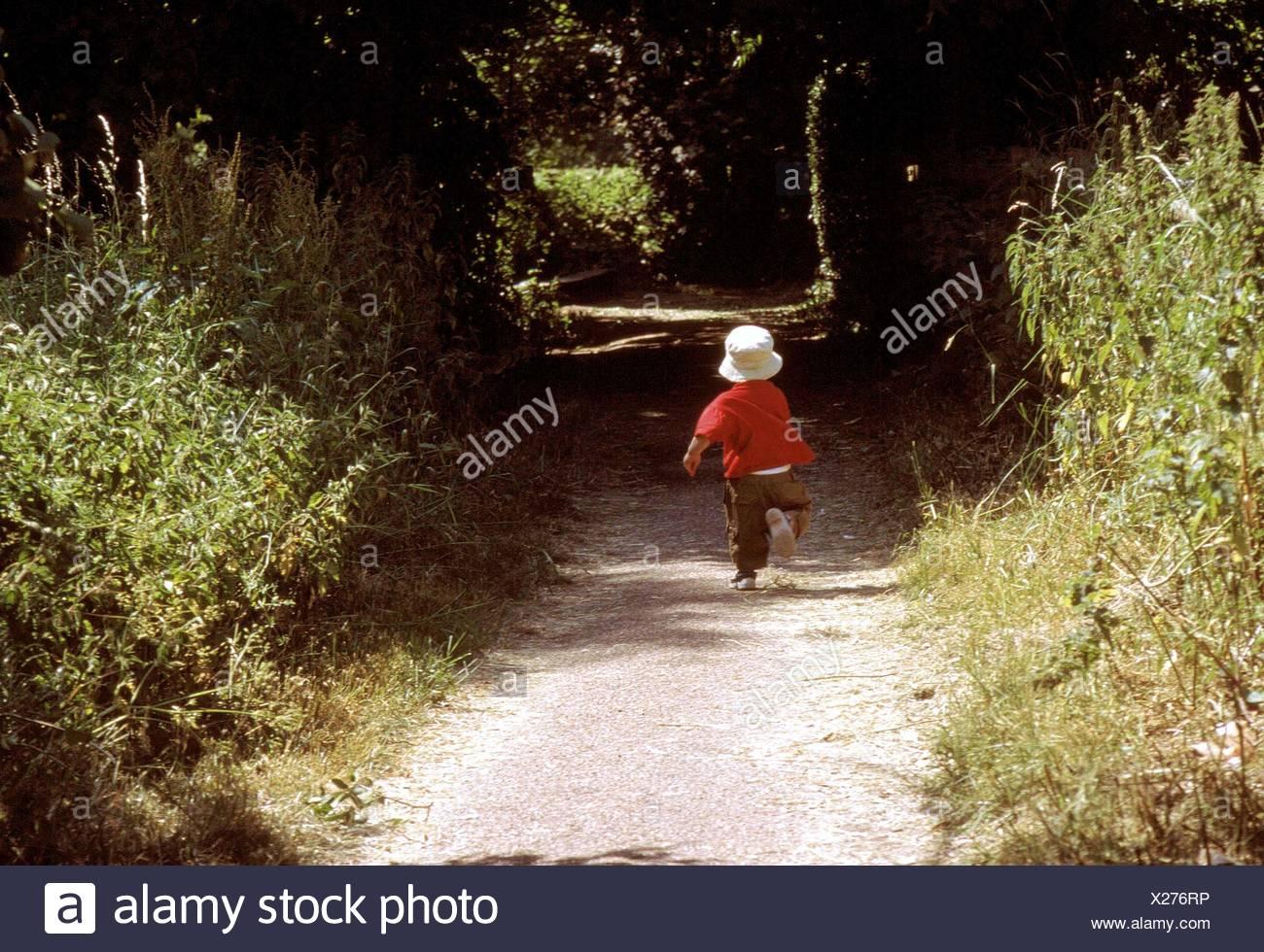 Jeune garçon courant le long chemin d'un pays Photo Stock
