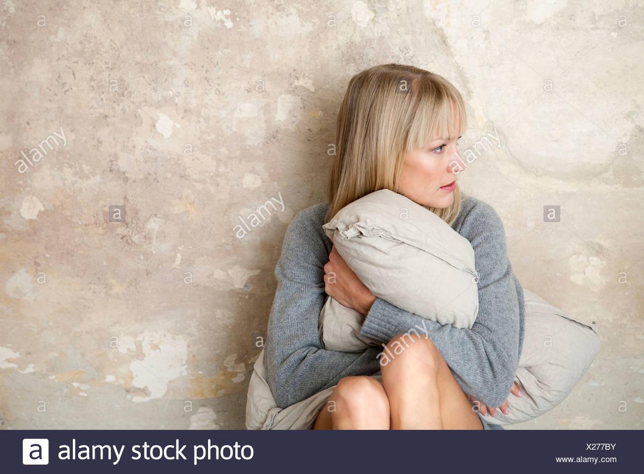 Woman sitting on floor avec oreiller Photo Stock