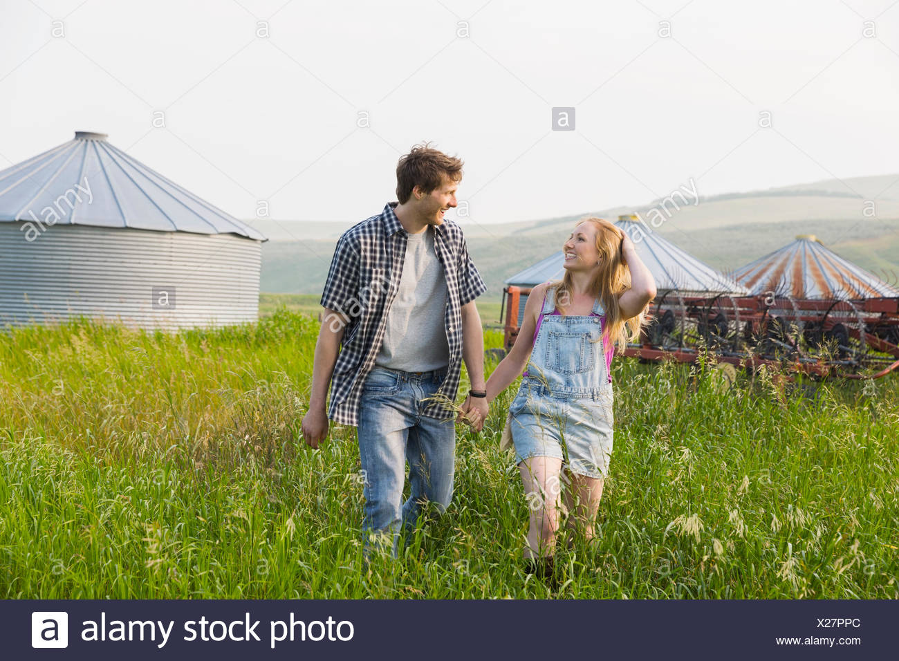 Couple holding hands and walking in rural field Photo Stock