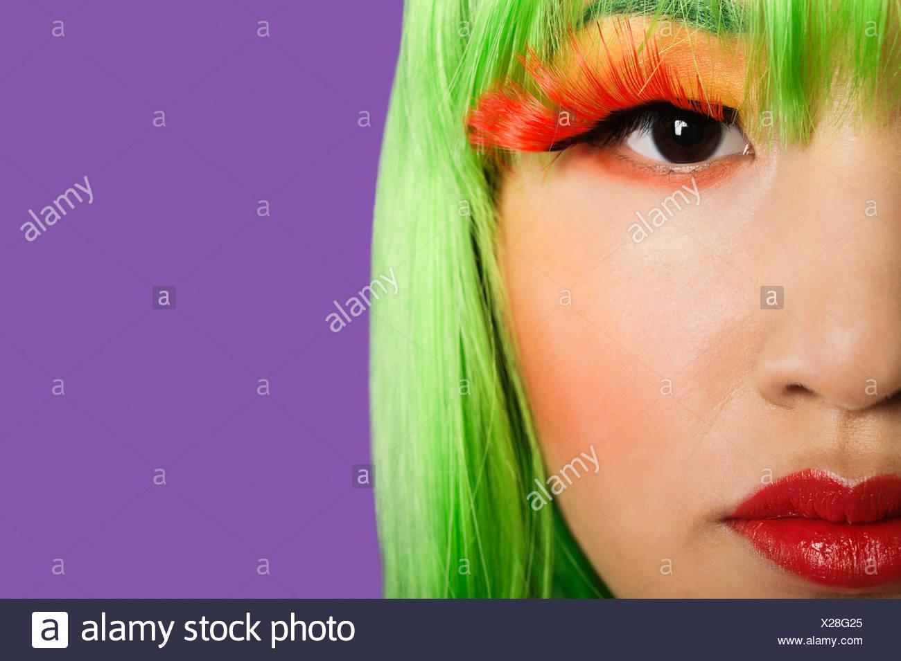 Portrait jeune femme portant de faux cils fond violet Photo Stock