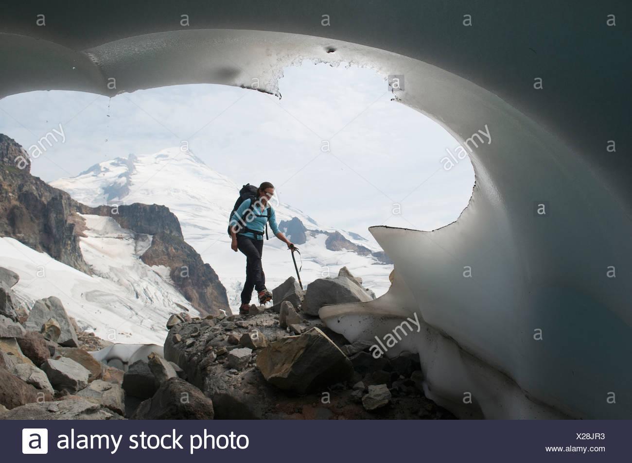 Une femme de l'alpinisme en passant un terminus glaciaire, Mount Baker Wilderness, Bellingham, Washington. Photo Stock