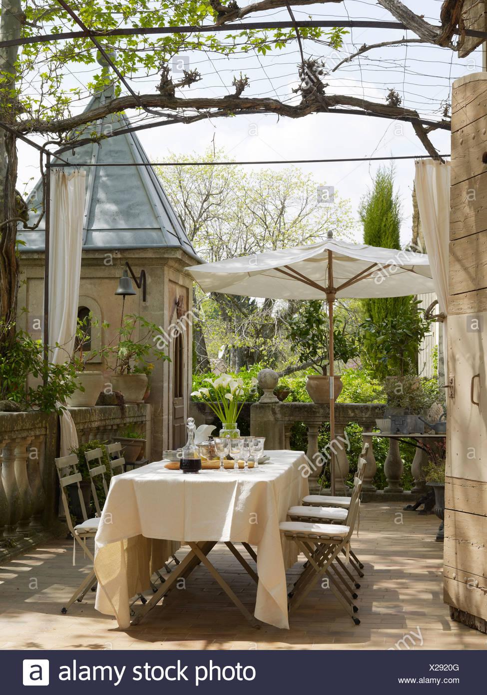 Terrasse d\'une vieille maison provençale avec une table couverte à ...