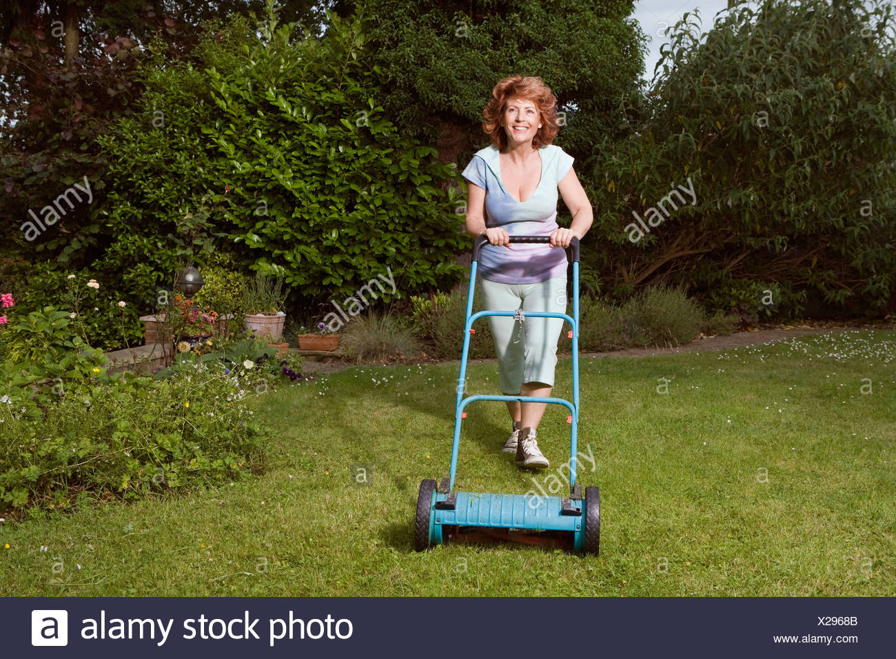 Mature Woman mowing lawn Photo Stock