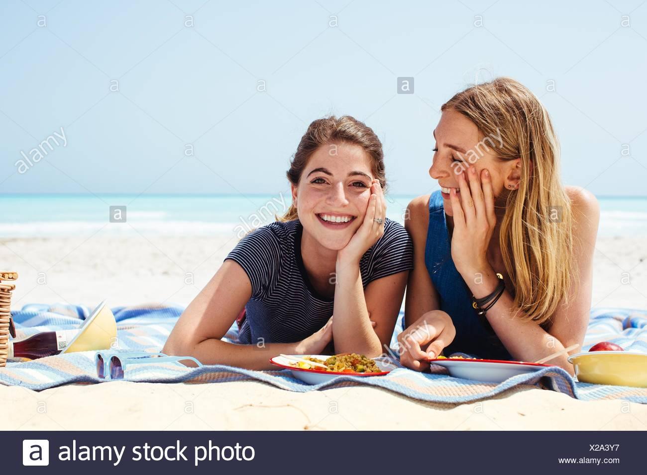 Portrait de deux jeunes amies lying on picnic blanket at beach Banque D'Images