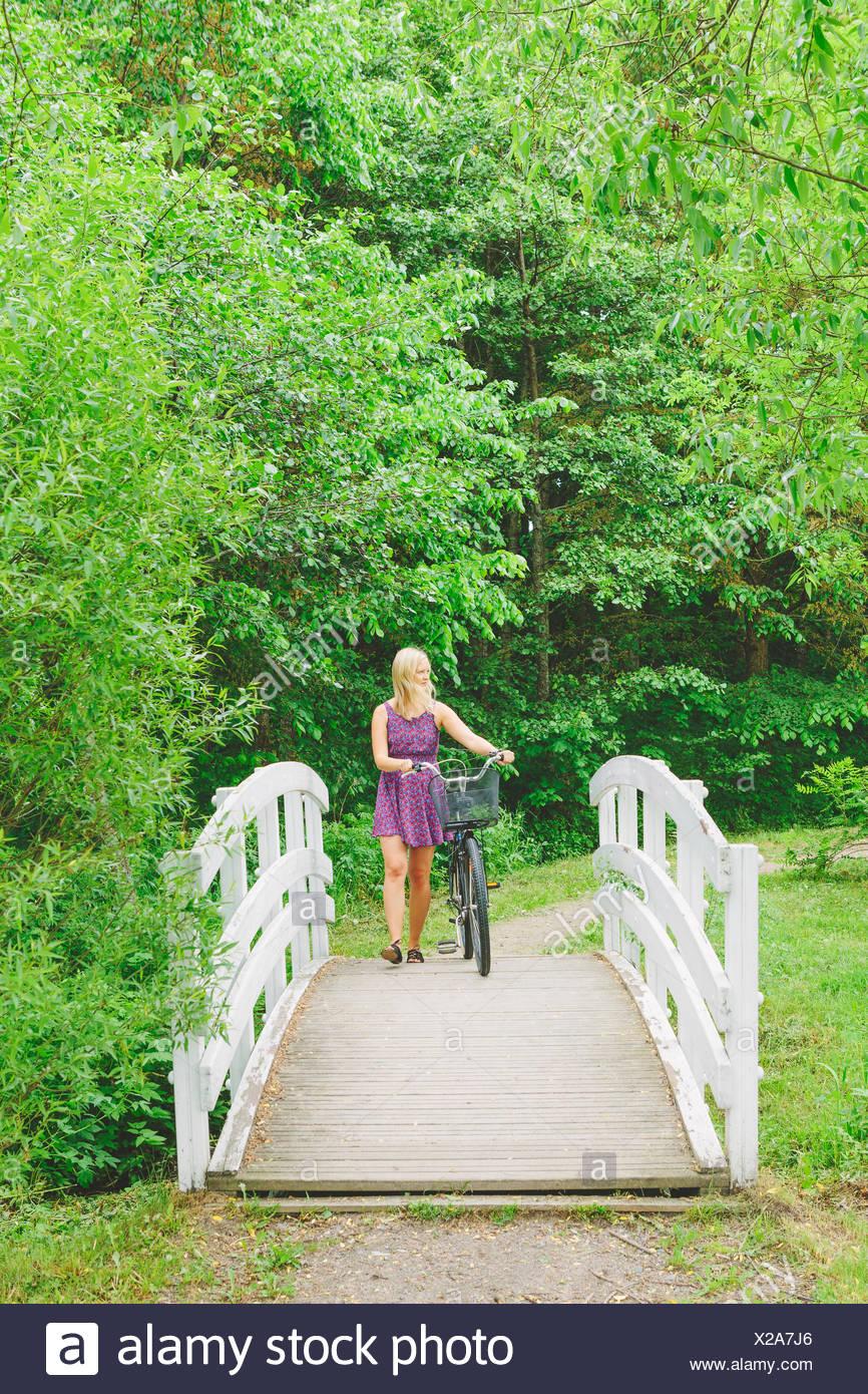 La Finlande, Helsinki, femme Aggelby, wheeling location marchant sur le pont du parc Banque D'Images