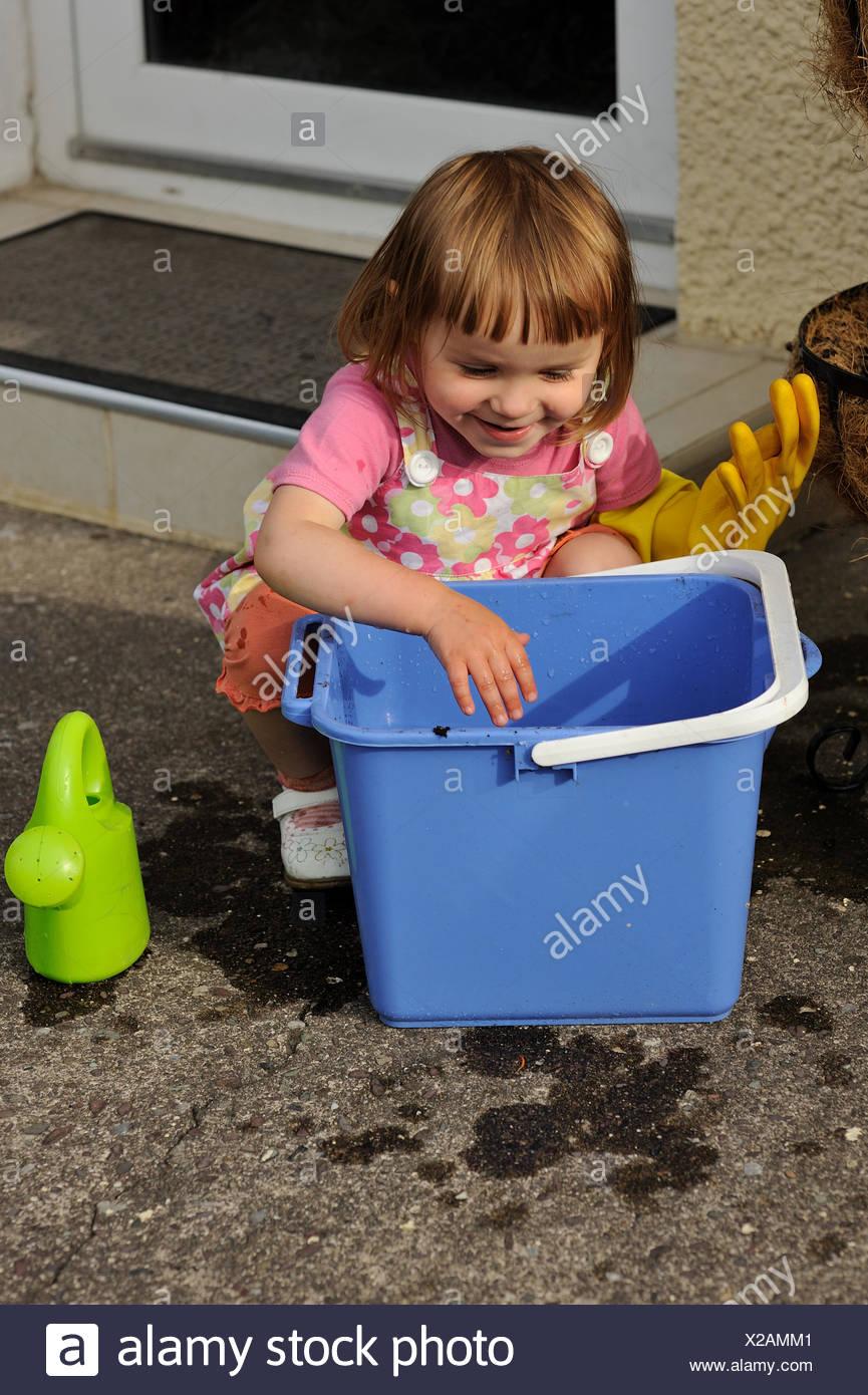 Accroupi à côté de fille un seau prêt à nettoyer Photo Stock