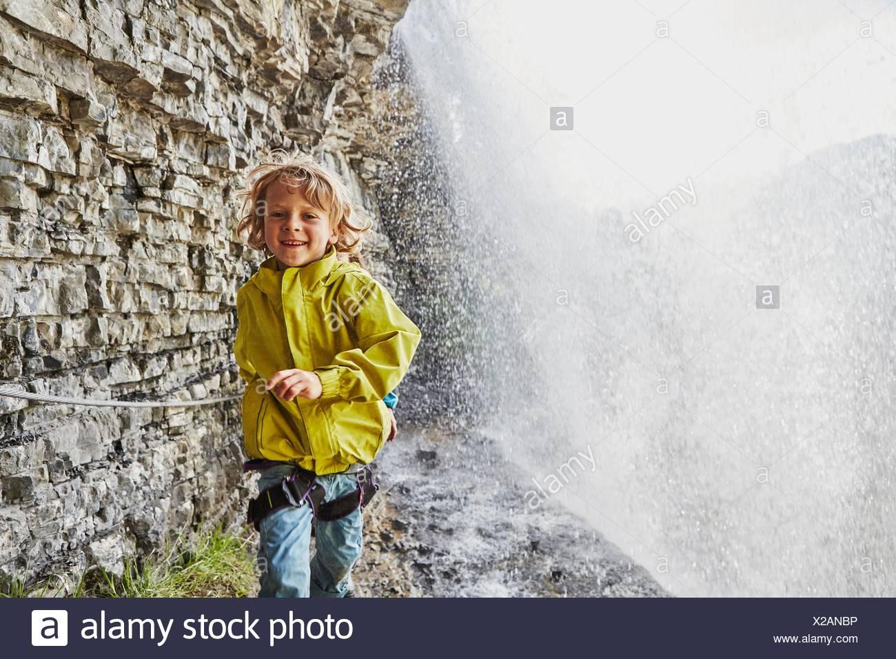 Jeune garçon marcher sous une cascade, smiling Photo Stock