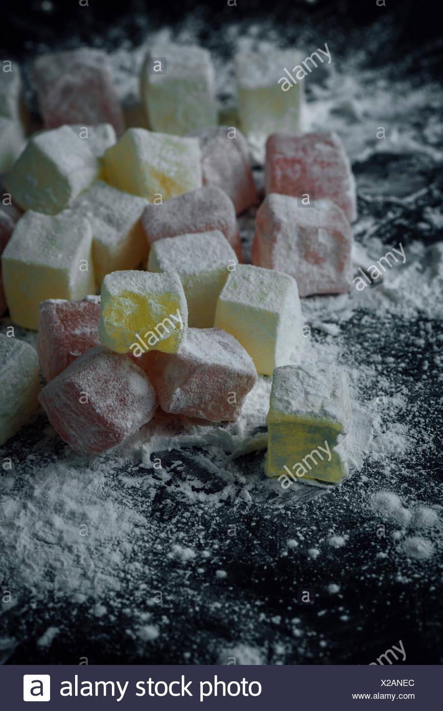 Classic loukoums en deux couleurs saupoudré avec de l'amidon, dont une est mordu. Photo Stock