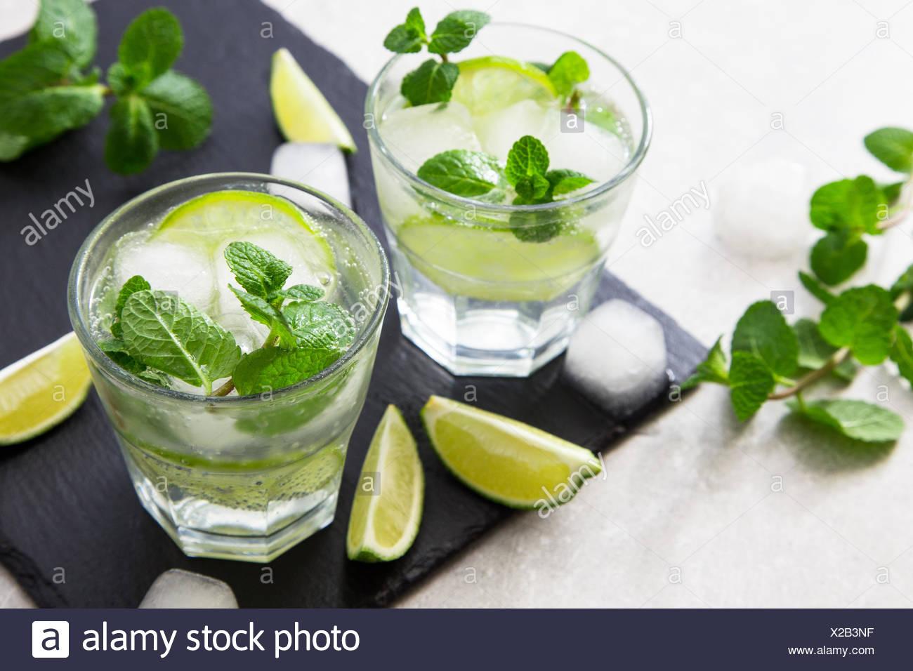 Rempli de limonade d'été mojito dans un verre sur un fond noir en ardoise et du conseil. Banque D'Images