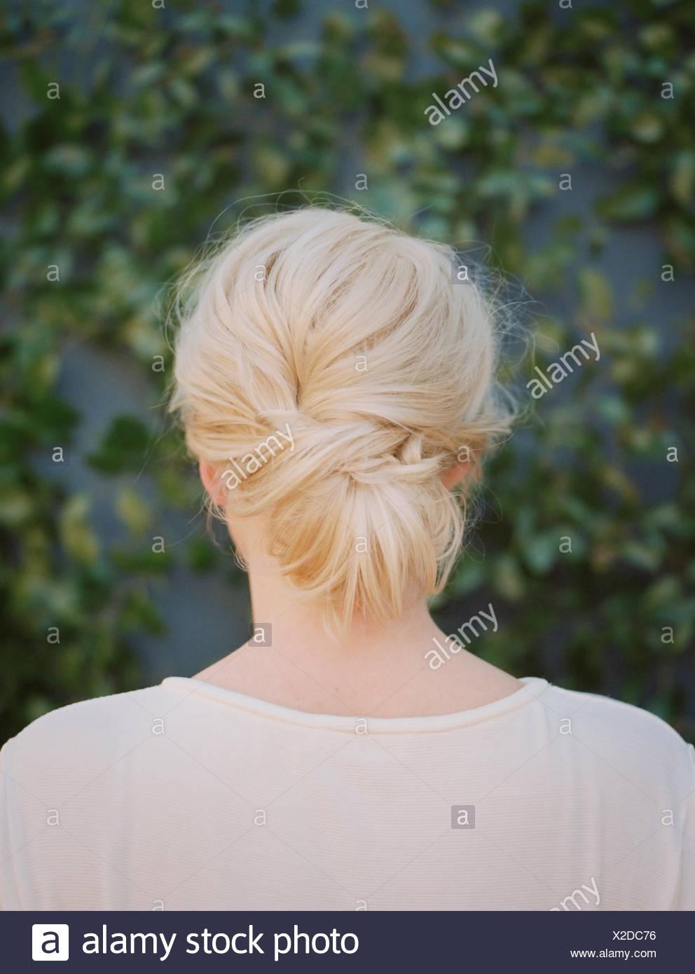 Une femme aux cheveux blonds disposés dans un noeud à la nuque. Photo Stock