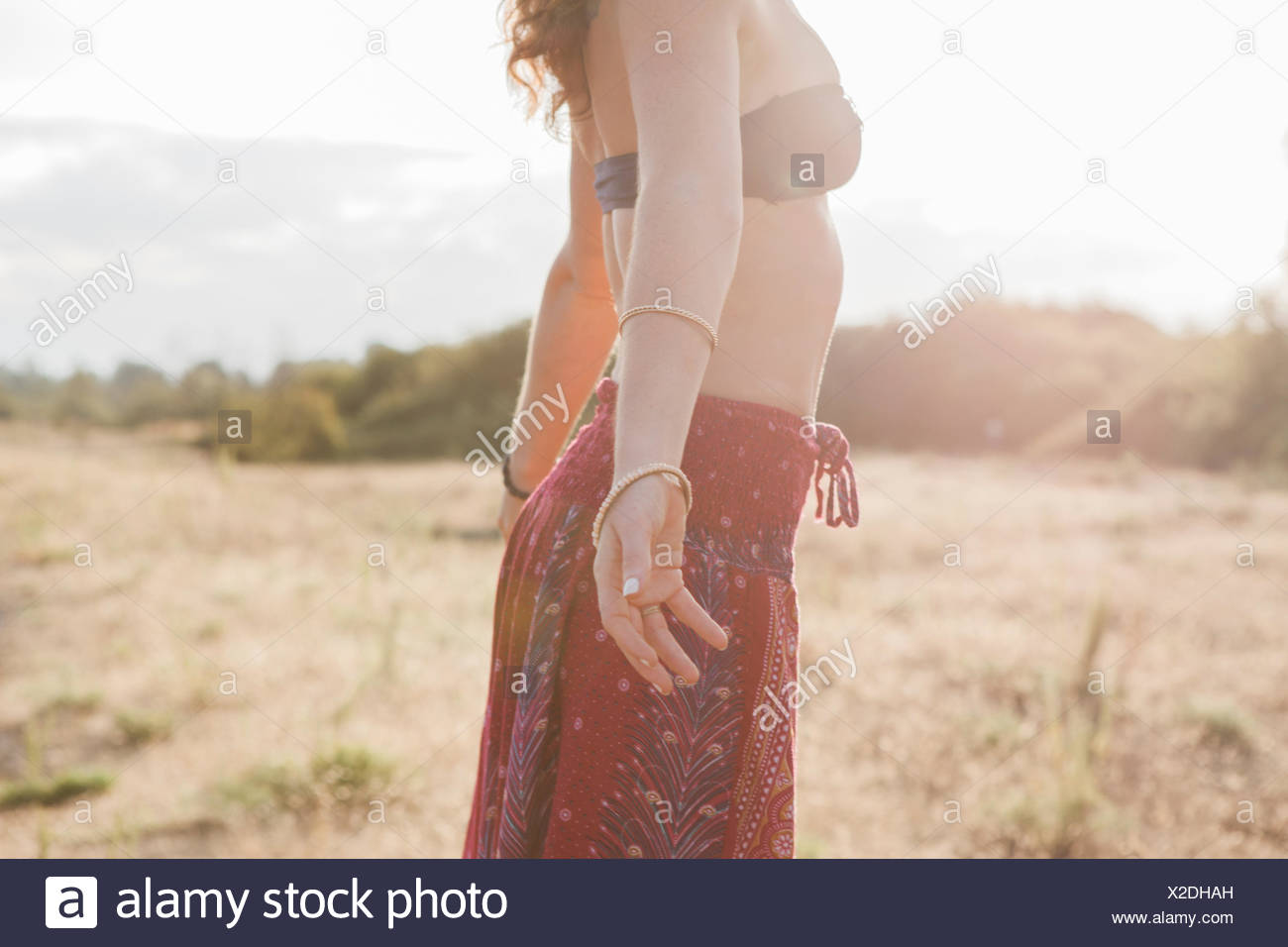 Boho woman in bikini top et jupe avec bras tendus à sunny rural field Photo Stock