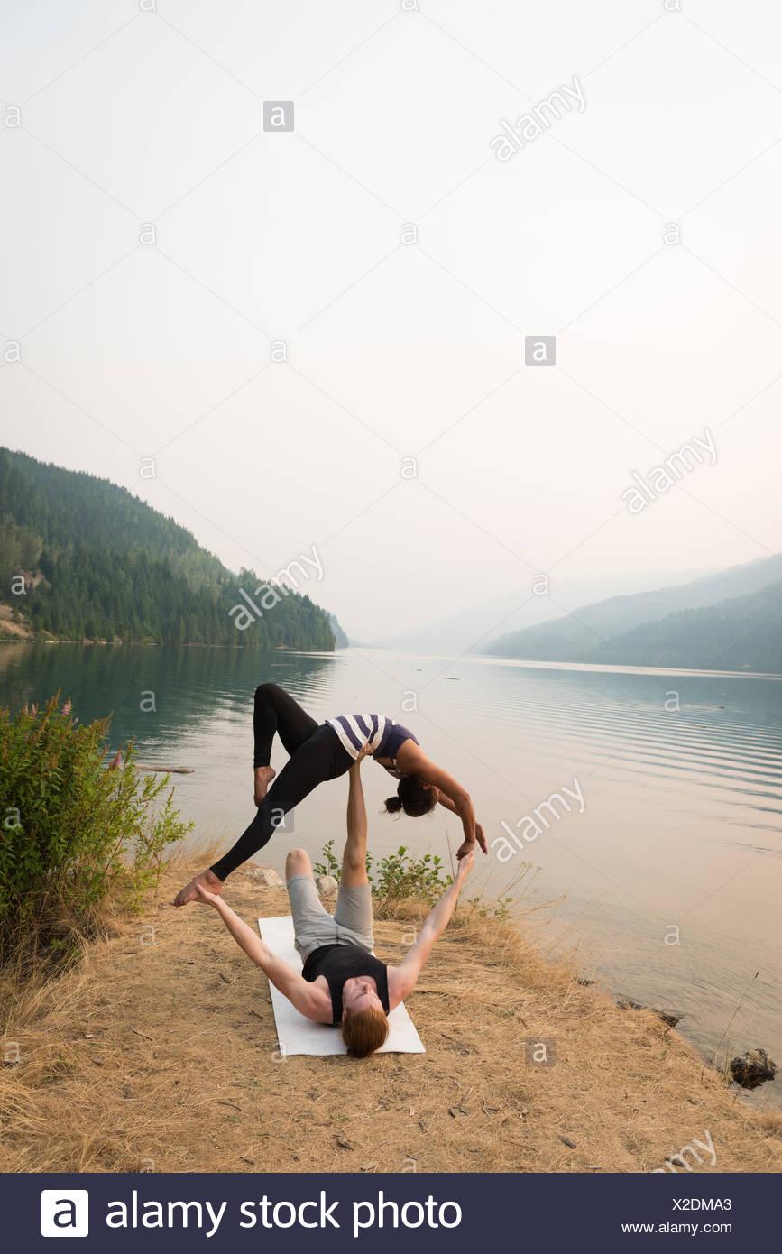 Monter couple practicing yoga acro dans un terrain verdoyant Photo Stock