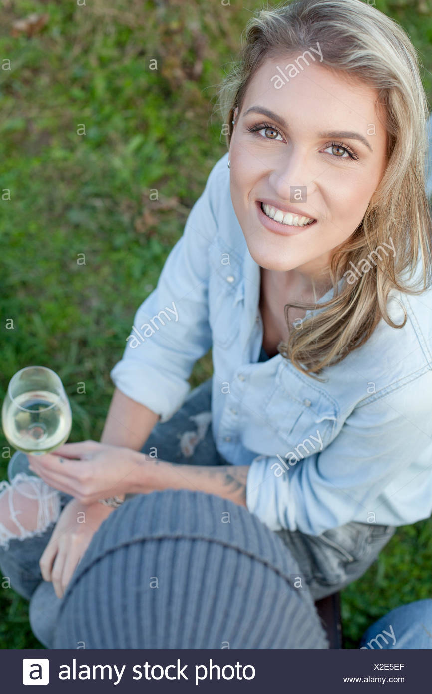 Femme aux cheveux blonds boire du vin sur garden party Photo Stock