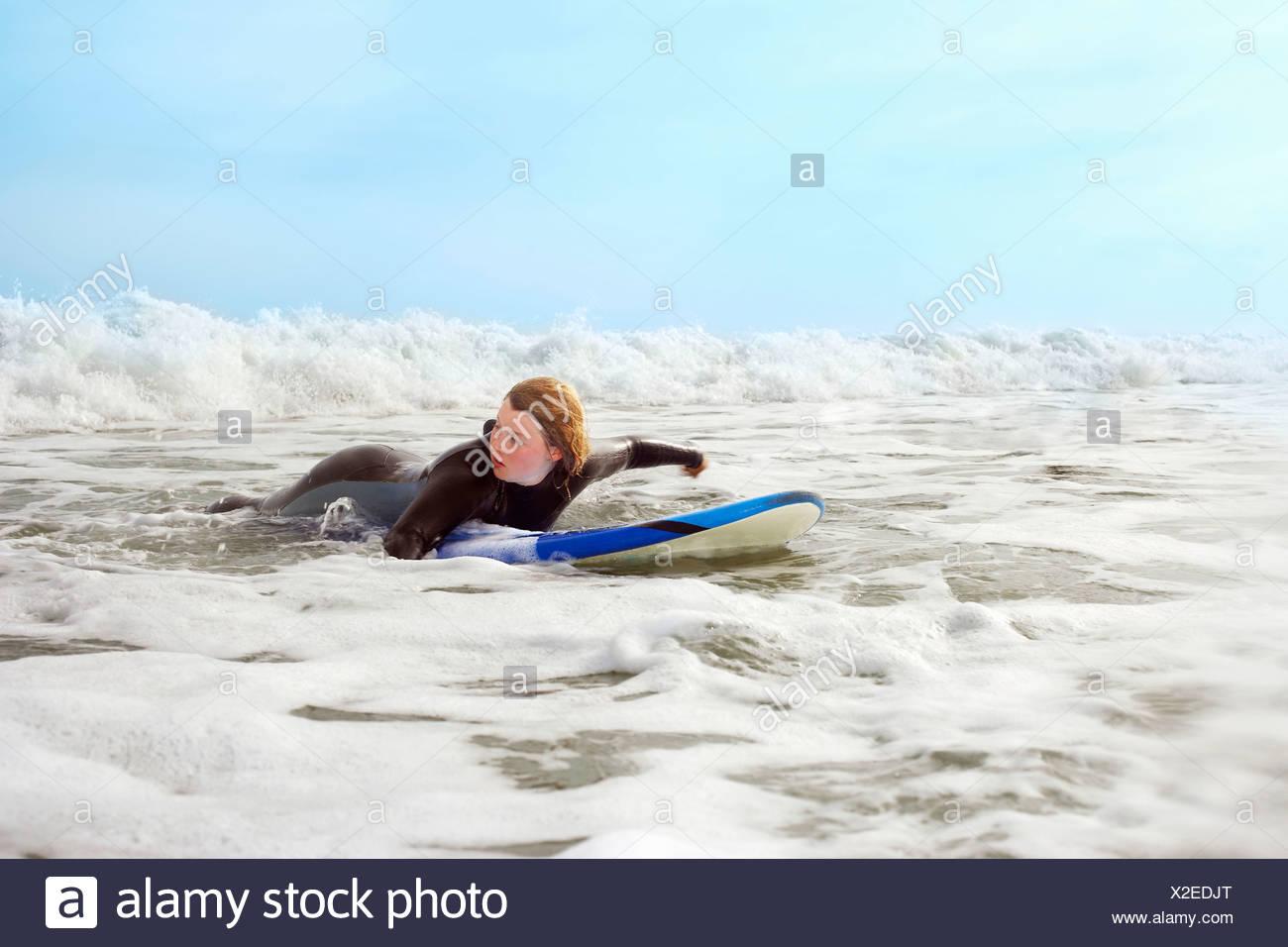 Femme couchée sur une planche de surf, bassin pour enfants Banque D'Images