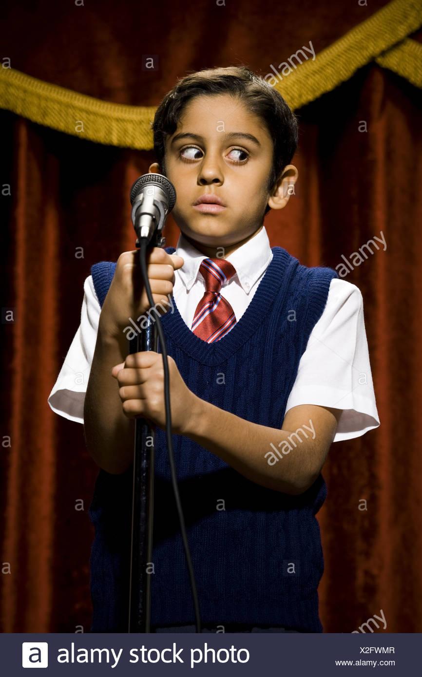 Garçon debout sur scène avec microphone et de grands yeux Photo Stock