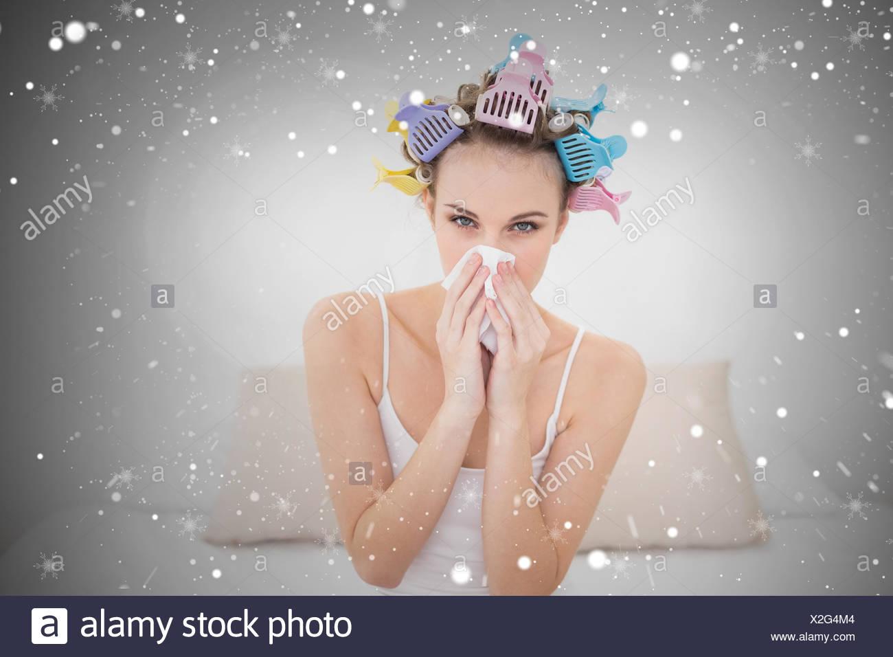 Cute natural brown haired woman in hair curlers éternuer dans un mouchoir Photo Stock